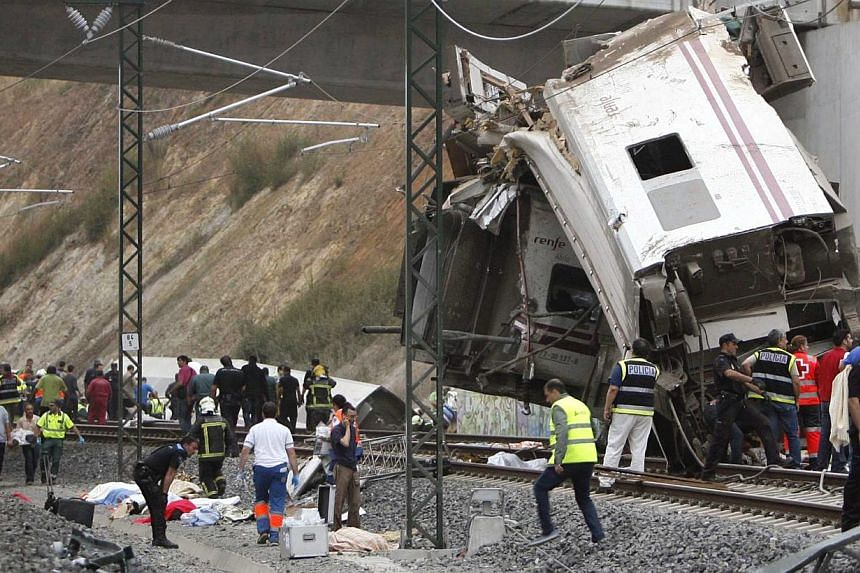 Emergency personnel respond to the scene of a train derailment in Santiago de Compostela, Spain, on July 24, 2013. At least 20 people reportedly died after the derailment. -- PHOTO: AP