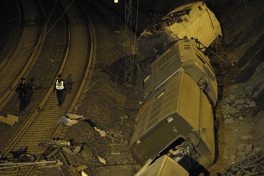 Spanish police officers walk next to derailed cars at the site of a train accident near the city of Santiago de Compostela early on July 25, 2013. -- PHOTO: AFP
