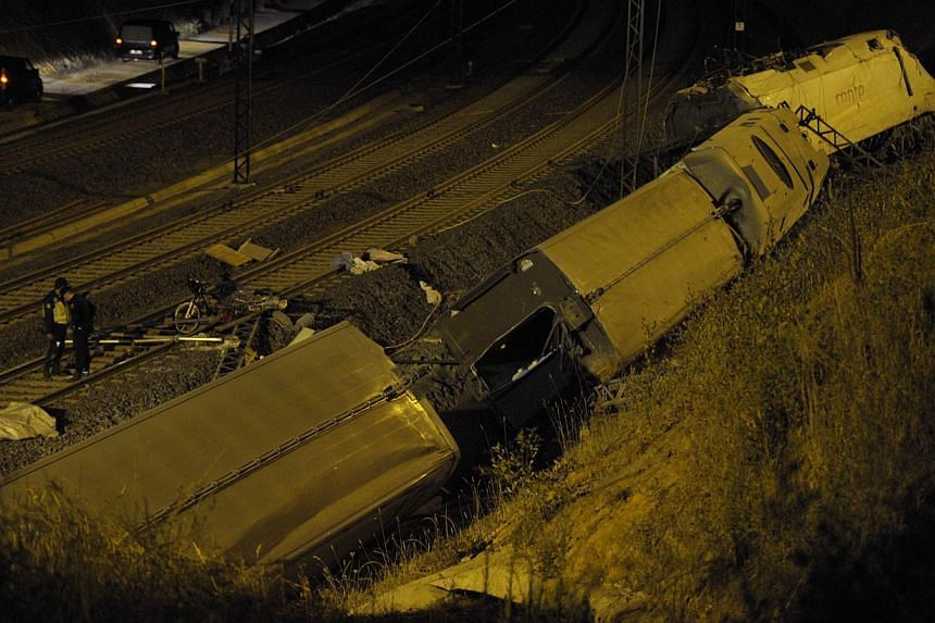A picture taken on July 25, 2013 shows derailed cars at the site of a train accident near the city of Santiago de Compostela. -- PHOTO: AFP