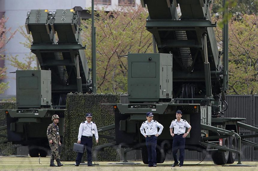 Japan Self-Defence Forces soldiers walk near Patriot Advanced Capability-3 (PAC-3) missiles at the Defence Ministry in Tokyo in this April 9, 2013 photo. Japan is likely to start considering acquiring the ability to launch pre-emptive military strike