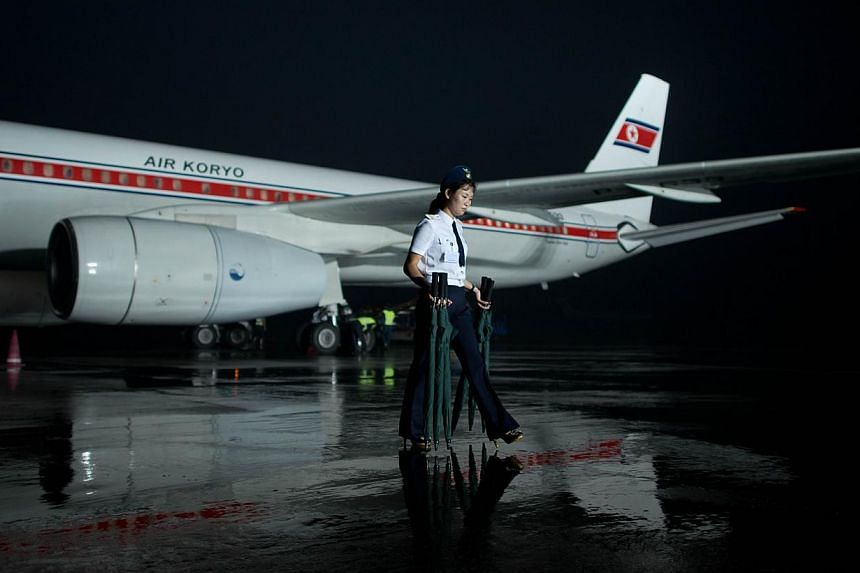 An Air Koryo staff member carries umbrellas from an aircraft arriving from Beijing on the tarmac at Pyongyang airport on July 24, 2013. North Korea is preparing to put its military hardware on show in a huge parade through Pyongyang on Saturday, the