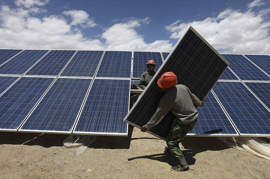 Workers install a solar panel in Jiuquan, Gansu province on Sunday, July 14, 2013. Chinese manufacturers are pressuring Beijing to take further measures to curb imports of raw materials used to make solar panels to help revive an ailing green-energy