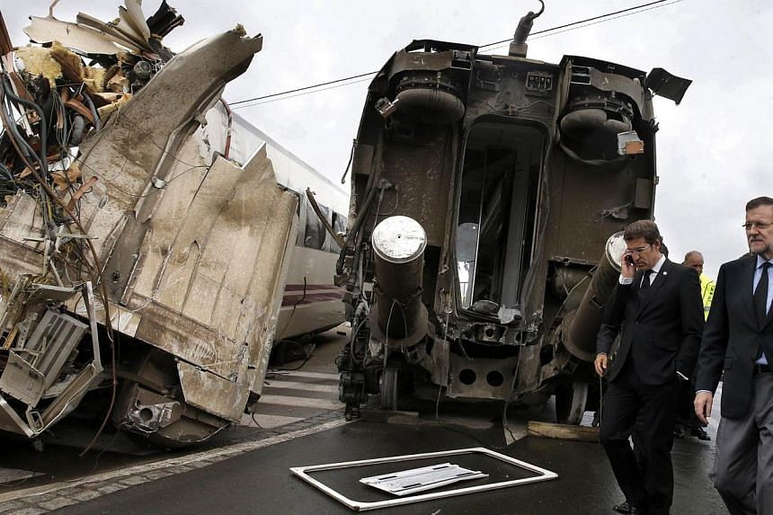 Spanish Prime Minister Mariano Rajoy (right) and Galicia's regional President Alberto Nunez Feijoo (second right) visit the site of a train accident near the city of Santiago de Compostela on Thursday, July 25, 2013. Some Americans and a Briton were
