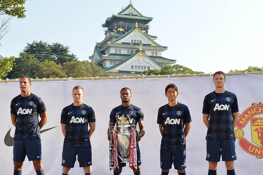 (From left) Rio Ferdinand, Tom Cleverley, Patrice Evra, Shinji Kagawa and Jonny Evans ofManchester United wear their new away uniforms for the 2013-14 season as they pose for photographers at a press briefing at Osaka Castle on Thursday, July 2