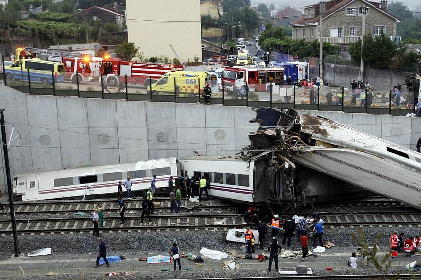 Rescuers work at the site of a train accident near the city of Santiago de Compostela on Wednesday, July 24, 2013. A train derailed outside the ancient north-western Spanish city of Santiago de Compostela on Wednesday evening, killing at least 77 peo
