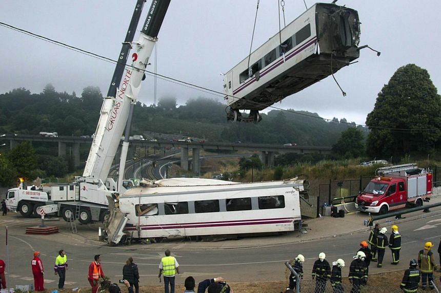 Derailed cars are removed as emergency personnel work at the site of a train accident in Santiago de Compostela, Spain on Thursday, July 25, 2013. -- PHOTO: AP