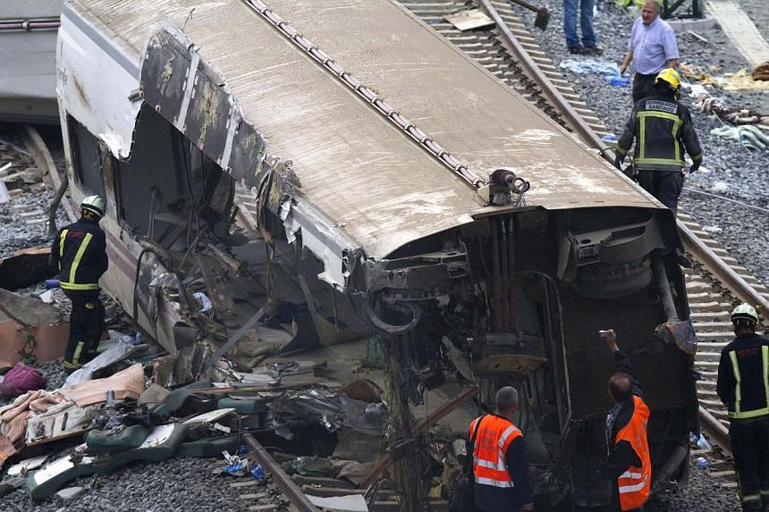 Rail personnel and firefighters inspect derailed cars at the site of a train accident in Santiago de Compostela, Spain on Thursday, July 25, 2013. -- PHOTO: AP
