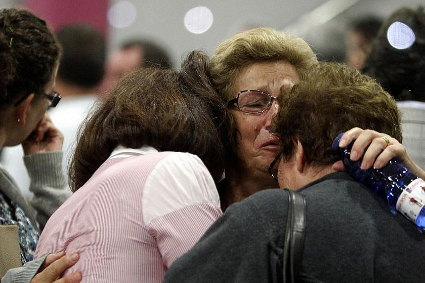 Relatives of the victims of a train accident react outside the Cersia building, where they are attended to by psychologists from the Red Cross in Santiago de Compostela on Thursday, July 25, 2013. -- PHOTO: AFP