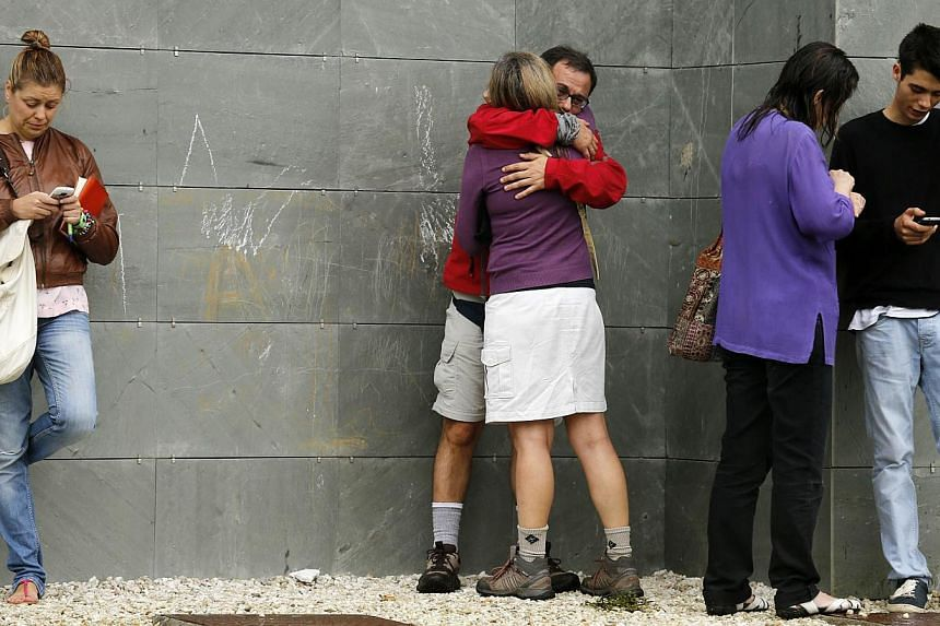Women react as relatives of victims of a train accident wait for news while gathering at an area where information will be released in Santiago de Compostela, Spain on Thursday, July 25, 2013. -- PHOTO: AP