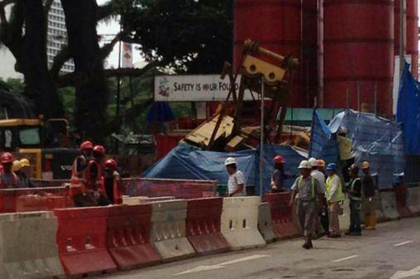 A construction crane at the National Art Gallery construction site on Coleman Street toppled over on Thursday morning around 9am.-- ST PHOTO: LIM YI HAN