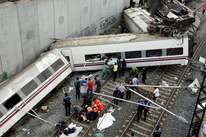 Rescuers tend to victims next to derailed cars at the site of a train accident near the city of Santiago de Compostela on Wednesday, July 24, 2013. -- FILE PHOTO: AFP