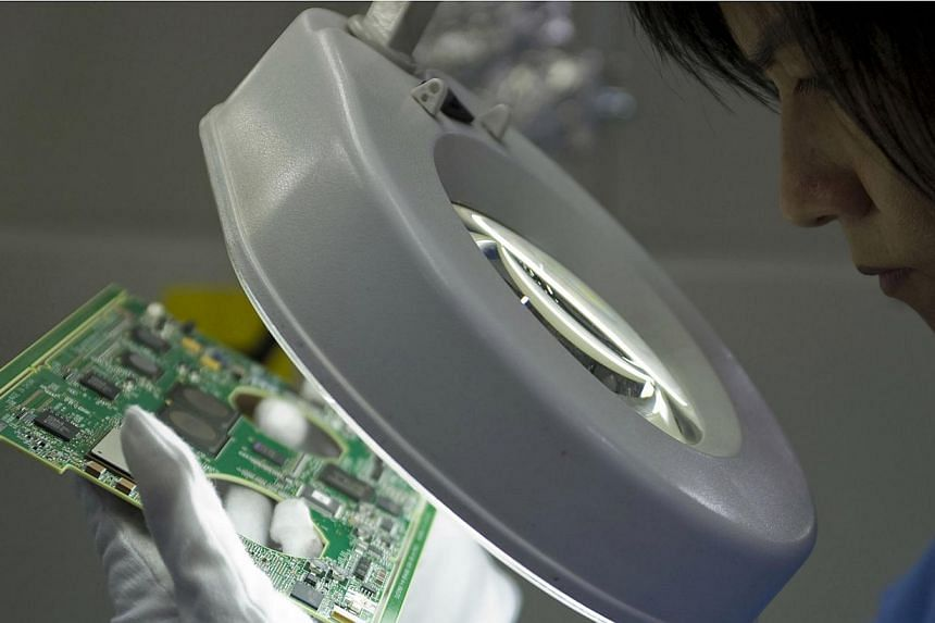A worker inspects a printed circuit board on the assembly line at the Venture Corp factory in Singapore, on Dec 15, 2008. Singapore's manufacturing output fell 5.9 per cent in June 2013 over the same month last year, dragged down by declines in the p