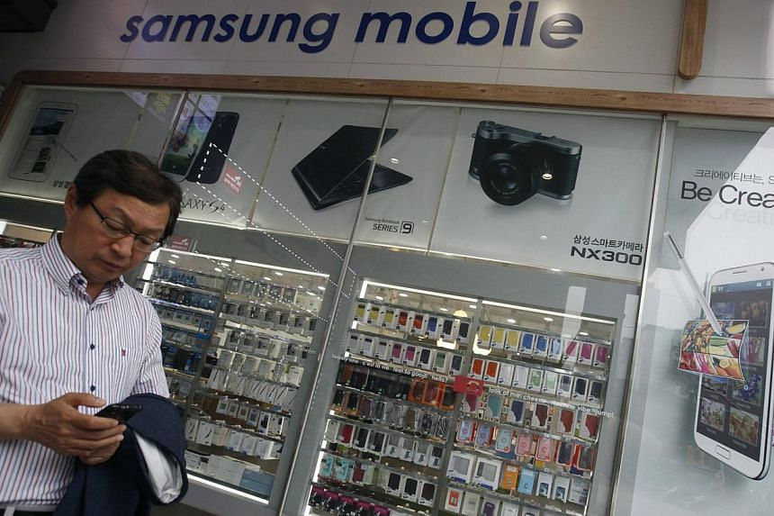 A man uses his mobile phone in front of a Samsung mobile shop in Seoul on July 4, 2013. Samsung Electronics Co Ltd is under mounting pressure to produce eye-catching new smartphones after its mobile business shrank 3.5 per cent in the second quarter,