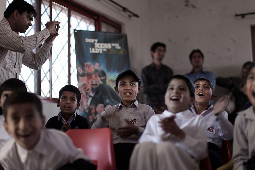 Pakistani orphans reacts while watching an early screening of the first episode of the animates Burka Avenger series, at an orphanage on the outskirts of Islamabad, Pakistan on Monday, March 25, 2013. -- FILE PHOTO: AP