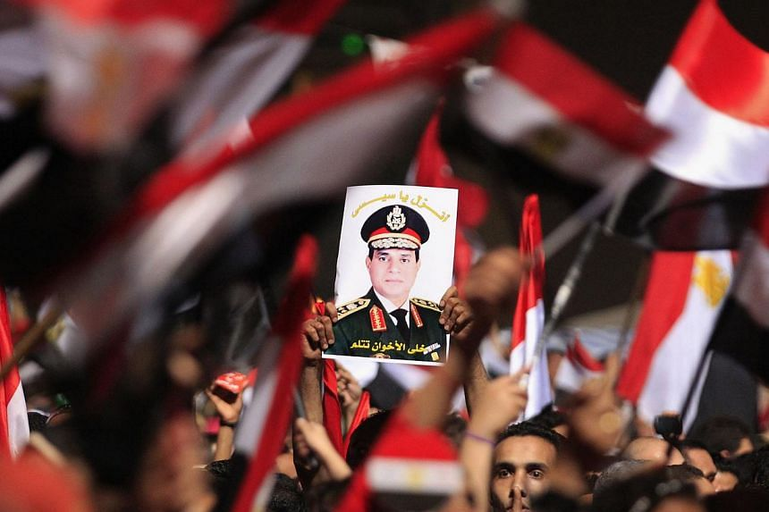 Protesters, who are against Egyptian President Mohamed Mursi, hold a poster featuring the head of Egypt's armed forces General Abdel Fattah al-Sisi in Tahrir Square in Cairo in this July 3, 2013 file photo. A deeply polarised Egypt braced for bloodsh