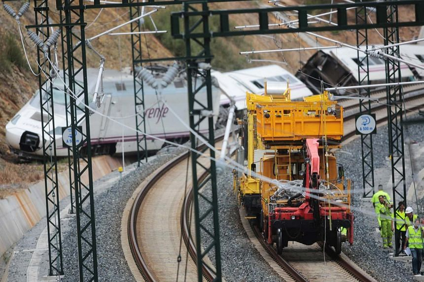 Rail workers inspect the tracks at the site of a train crash near Santiago de Compostela, north-western Spain, on July 25, 2013. The driver of a Spanish train that derailed, killing at least 80 people, was under police guard in hospital on Friday aft