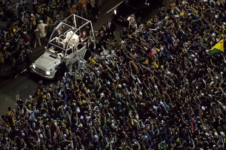 Pope Francis greets from his popemobile as he makes his way through the crowds lining the Copacabana beachfront in Rio de Janeiro, Brazil on Thursday, July 25, 2013. -- PHOTO: AP