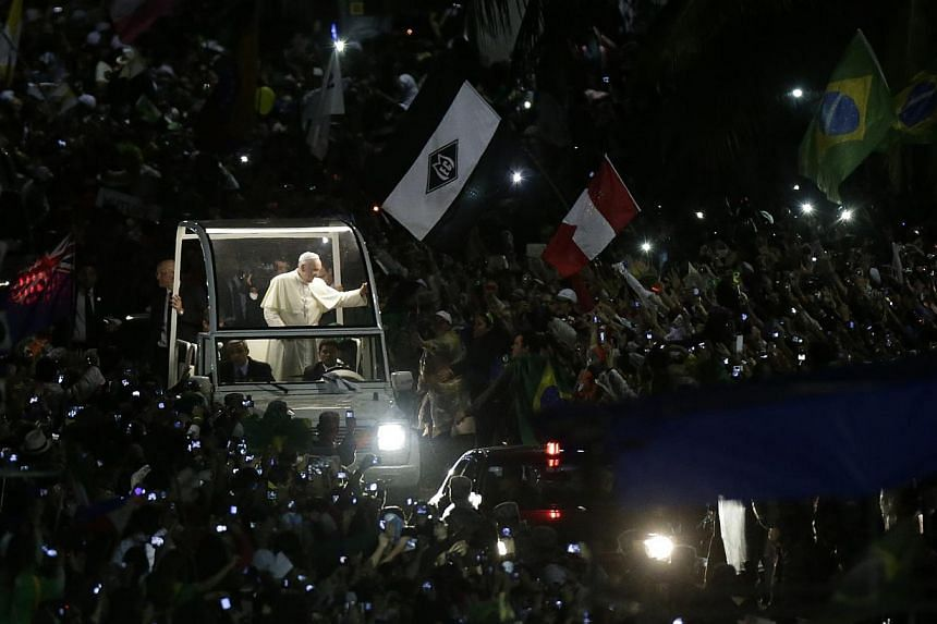 Pope Francis greets Catholic faithful during his arrival at Copacabana beach in Rio de Janeiro on July 25, 2013. Pope Francis is on the fourth day of his week-long visit for World Youth Day. -- PHOTO: REUTERS