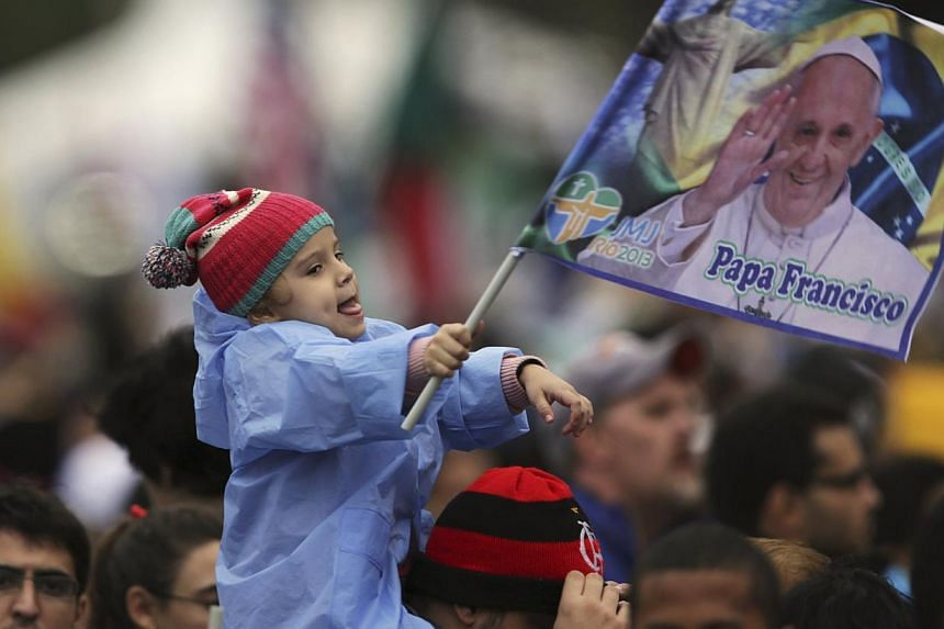 A child waves a flag with an image of Pope Francis while waiting for his arrival at Copacabana beach in Rio de Janeiro on July 25, 2013. -- PHOTO: REUTERS
