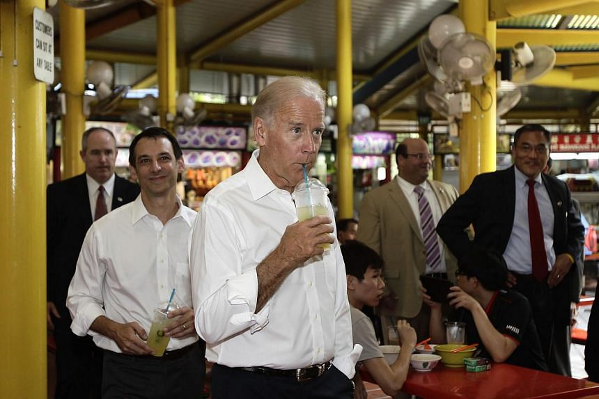 US Vice-President Joe Biden (centre) drinks his lime juice during an impromptu visit to Adam Road Hawker Centre in Singapore on Friday, July 26, 2013. -- PHOTO: REUTERS