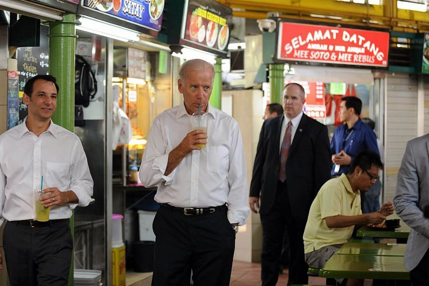 US Vice-President Joe Biden (front centre) walks with his son-in-law Howard Krien (left) during a visit to Adam Road Hawker Centre in Singapore on Friday, July 26, 2013. -- PHOTO: AFP