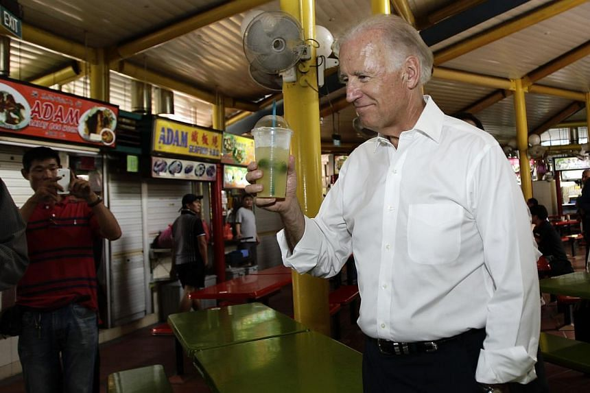 US Vice-President Joe Biden gestures to a stall handler during an impromptu visit to Adam Road Hawker Centre in Singapore on Friday, July 26, 2013. -- PHOTO: REUTERS