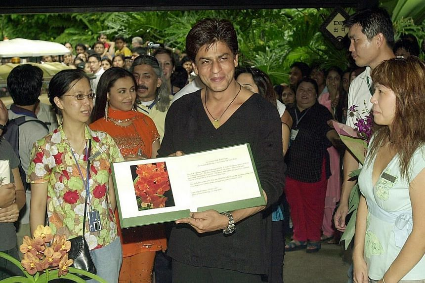 Bollywood actor Shah Rukh Khan holds up a picture of Ascocenda Shah Rukh Khan, an orchid which was named after him at the National Orchid Garden. -- BH FILE PHOTO: MOHD KHALID BABA