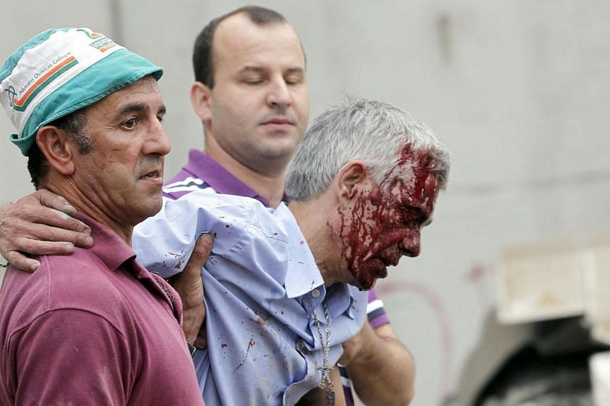 Wounded train driver Francisco Jose Garzon Amo is evacuated by two men after the train accident near the city of Santiago de Compostela on Wednesday, July 24, 2013. Spanish police said on Friday, July 26, 2013, they have formally detained the driver