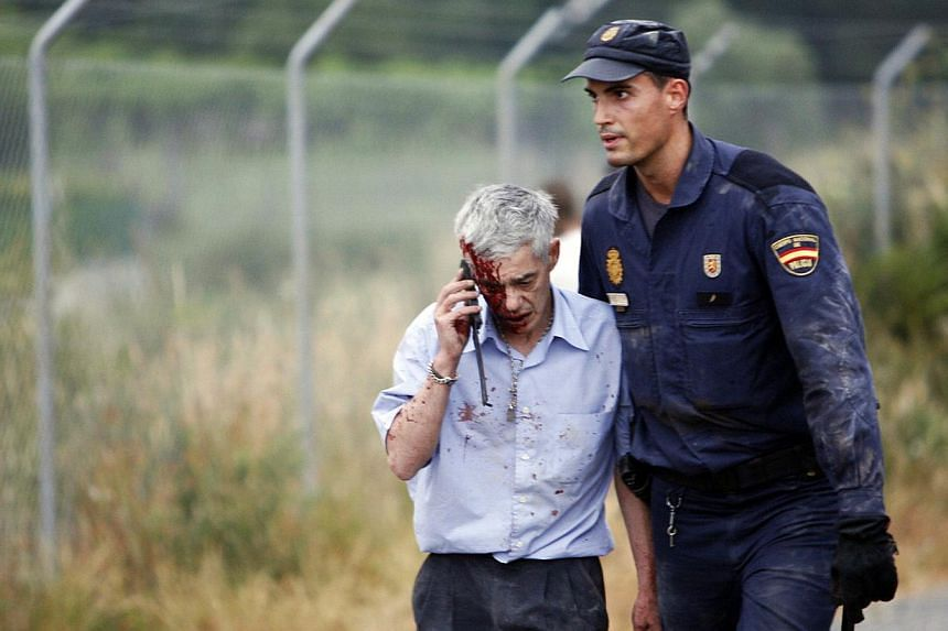An injured man, identified by Spanish newspapers El Pais and El Mundo as the train driver Francisco Jose Garzon, is helped by a policeman after a train crashed near Santiago de Compostela, north-western Spain on Wednesday, July 24, 2013. Spanish poli