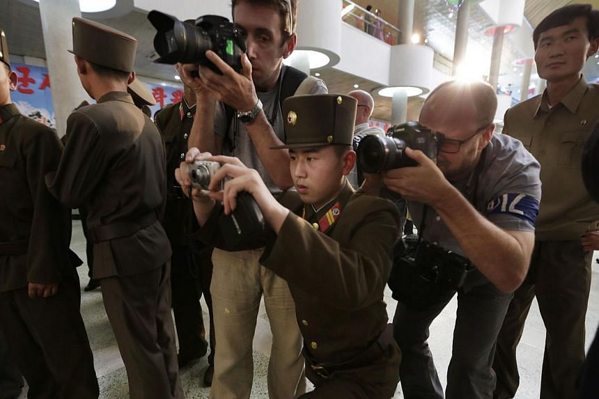 A North Korean soldier takes a group photo for other soldiers next to foreign news photographers as they visit the Kimilsungia-Kimjongilia exhibition in Pyongyang on Friday, July 26, 2013. -- PHOTO: REUTERS