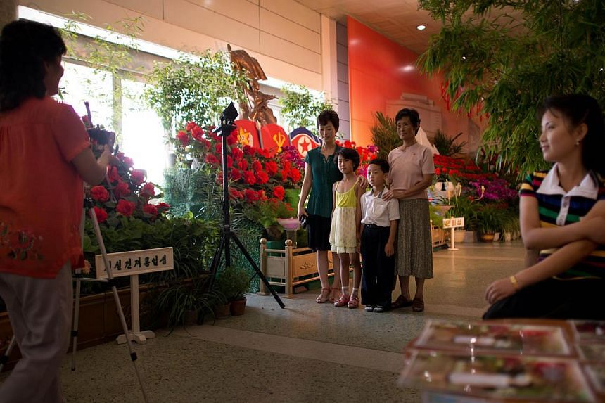 A North Korean family (centre) is seen posing for a photo as they visit a Kimilsungia flower festival in Pyongyang on Friday, July 26, 2013. -- PHOTO: AFP