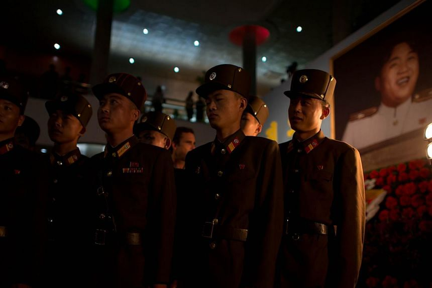 North Korean soldiers stand before a portrait of late North Korean leader Kim Il Sung (back right) as they visit a Kimilsungia flower festival in Pyongyang on Friday, July 26, 2013. -- PHOTO: AFP