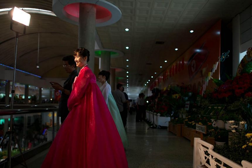 A woman wearing a traditional North Korean dress attends a Kimilsungia flower festival in Pyongyang on Friday, July 26, 2013. -- PHOTO: AFP