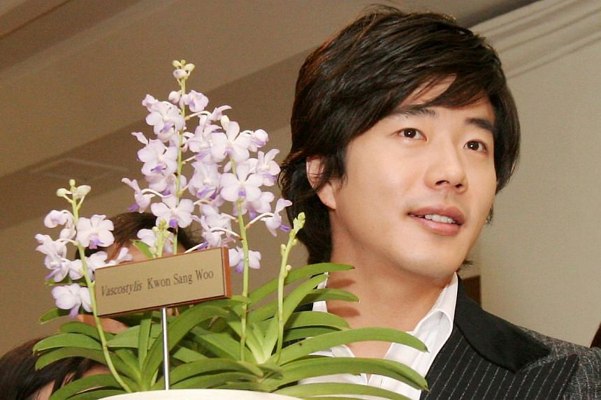 Korean actor Kwon Sang Woo holds an orchid that was named after him at the National Orchid Garden. -- TNP FILE PHOTO: GAVIN FOO
