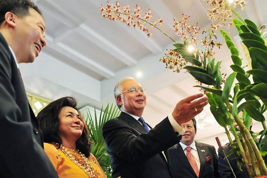 Malaysian Prime Minister Datuk Seri Mohd Najib Bin Tun Haji Abdul Razak (third from left) reaches out to touch a flower at the National Orchid Garden's Burkhill Hall, at a ceremony in which an orchid - the Dendrobium Najib Rosmah - was named in honou