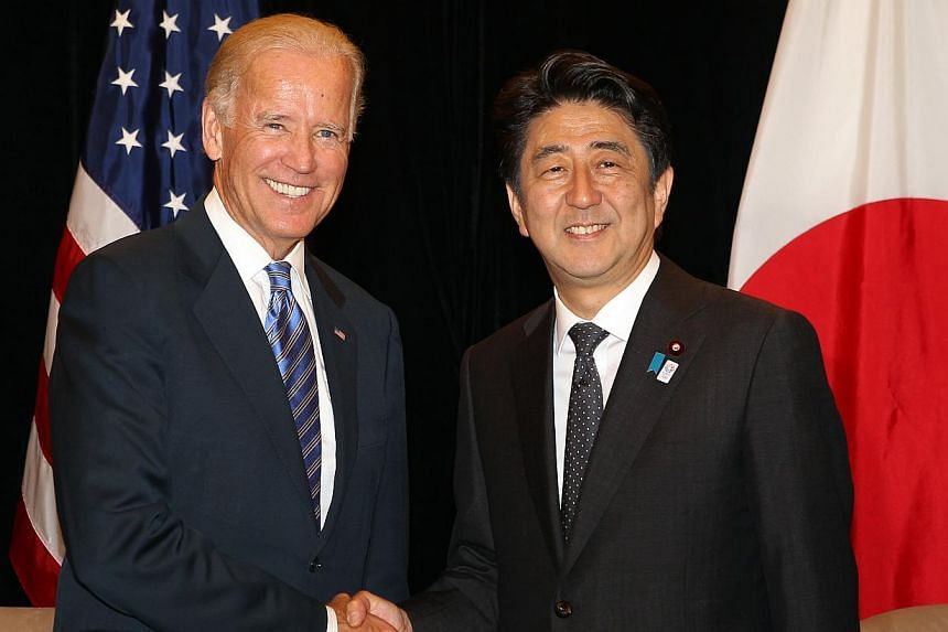 US Vice-President Joe Biden (left) shakes hands with Japan Prime Minister Shinzo Abe at the Ritz Carlton on Friday, July 26, 2013. -- ST PHOTO: LAU FOOK KONG