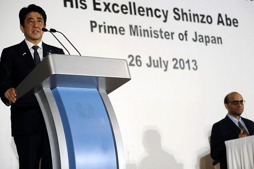 Japan's Prime Minister Shinzo Abe (left) speaks next to Singapore's Deputy Prime Minister and Finance Minister Tharman Shanmugaratnam during the 33rd Singapore Lecture at The Ritz Carlton in Singapore on Friday, July 26, 2013. Mr Abe called on Friday