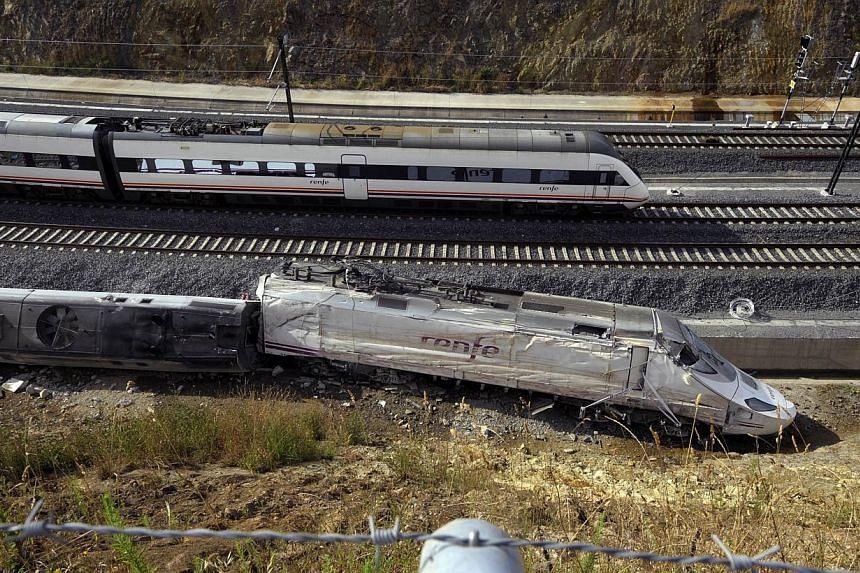 A train passes the scene of a train crash at Angrois, near Santiago de Compostela, Spain on Friday, July 26, 2013. -- PHOTO: AFP