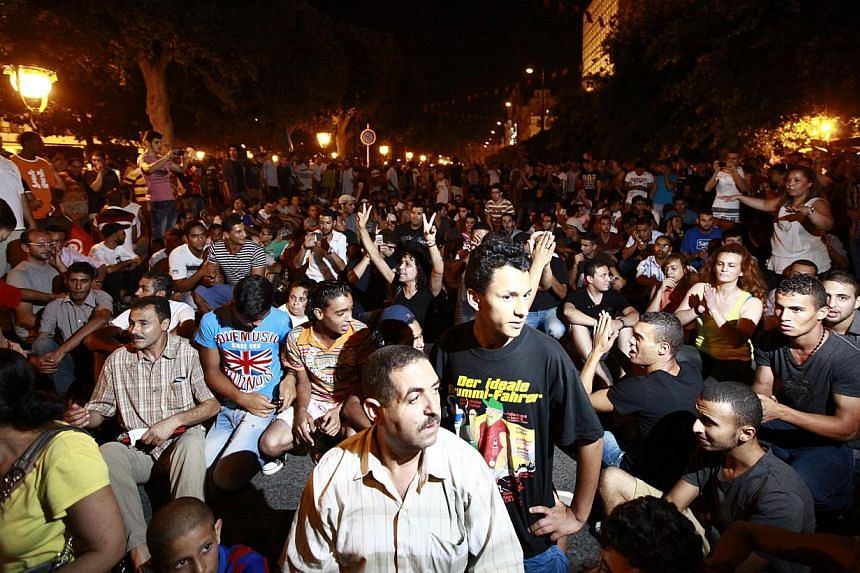 Tunisians gather to protest the killing of opposition politician Mohamed Brahimi in Tunis on Thursday, July 25, 2013. Tunisia's president declared a day of mourning on Friday, July 26, 2013, after gunmen shot dead a leading opposition figure, plungin