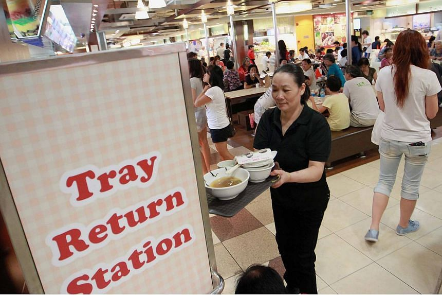 A customer at a Kuofu foodcourt placing her tray at a tray return station. Tray return points and racks will be fitted at all hawker centres in Singapore in the next two years, the National Environment Agency said on Saturday.-- ST PHOTO: NEO X