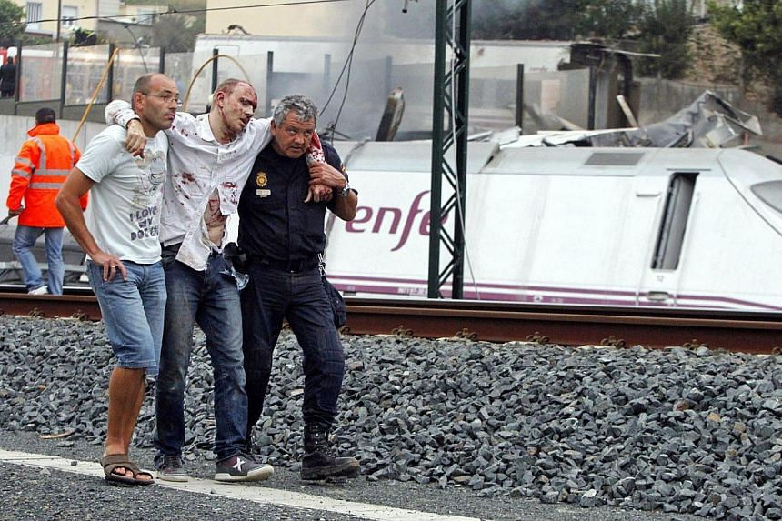 Rescue workers help a victim of a train crash near Santiago de Compostela, north-western Spain, on July 24, 2013. After the deadly high-speed train crash that struck on the rails below the nearby embankment on July 24, locals in Angrois, a hamlet on