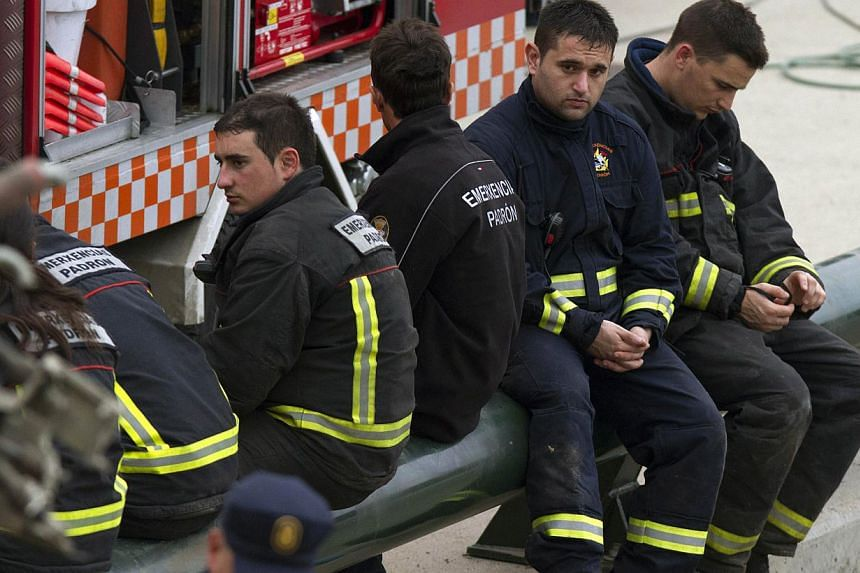 Emergency personnel take a break while working at the site of a train accident in Santiago de Compostela, Spain, on July 25, 2013. After the deadly high-speed train crash that struck on the rails below the nearby embankment on July 24, locals in Angr