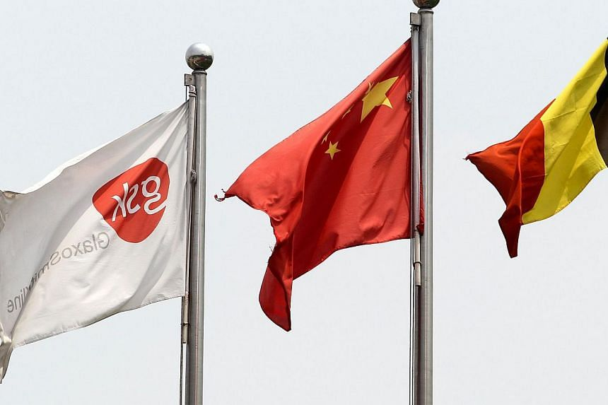 A flag of Glaxo Smith Kline (GSK) (left) flies over its facilities in Shanghai on July 25, 2013.At least 18 more people have been detained in China in connection with a corruption scandal involving British drugmaker GlaxoSmithKline (GSK), state