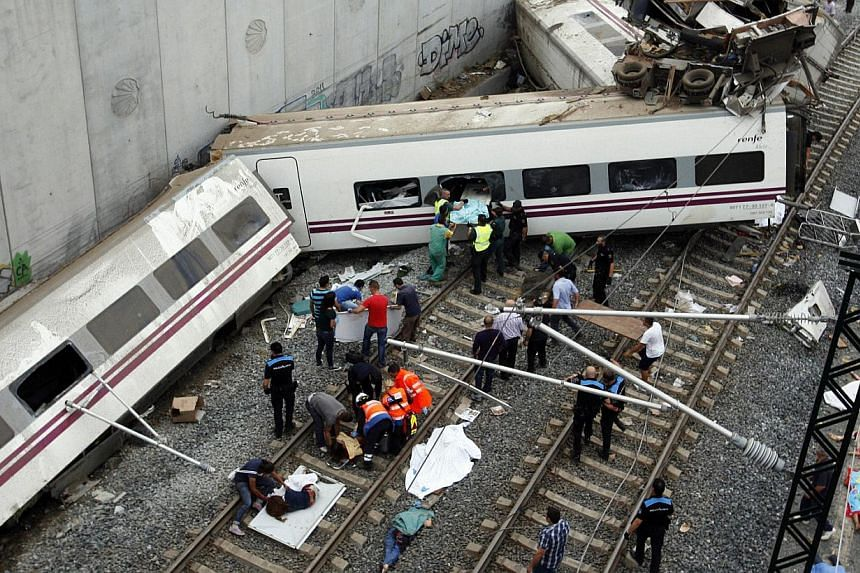 Rescuers tend to victims next to derailed cars at the site of a train accident near the city of Santiago de Compostela on July 24, 2013. After the deadly high-speed train crash that struck on the rails below the nearby embankment on Wednesday, locals