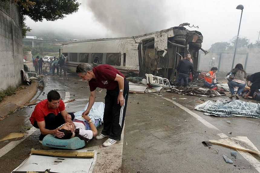 Two men comforting an injured woman next to a derailed car following a train accident near the city of Santiago de Compostela on July 24, 2013.After the deadly high-speed train crash that struck on the rails below the nearby embankment on Wedne