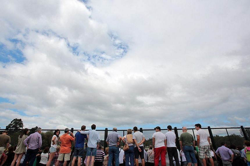 Onlookers view the wreckage of a train crash near Santiago de Compostela, north-western Spain, on July 25, 2013. After the deadly high-speed train crash that struck on the rails below the nearby embankment on July 24, locals in Angrois, a hamlet on t