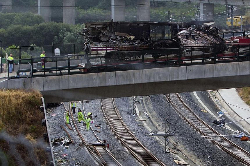 A burned out train carriage is taken away on a flat-bed truck in Santiago de Compostela, Spain, on July 26, 2013. After the deadly high-speed train crash that struck on the rails below the nearby embankment on July 24, locals in Angrois, a hamlet on