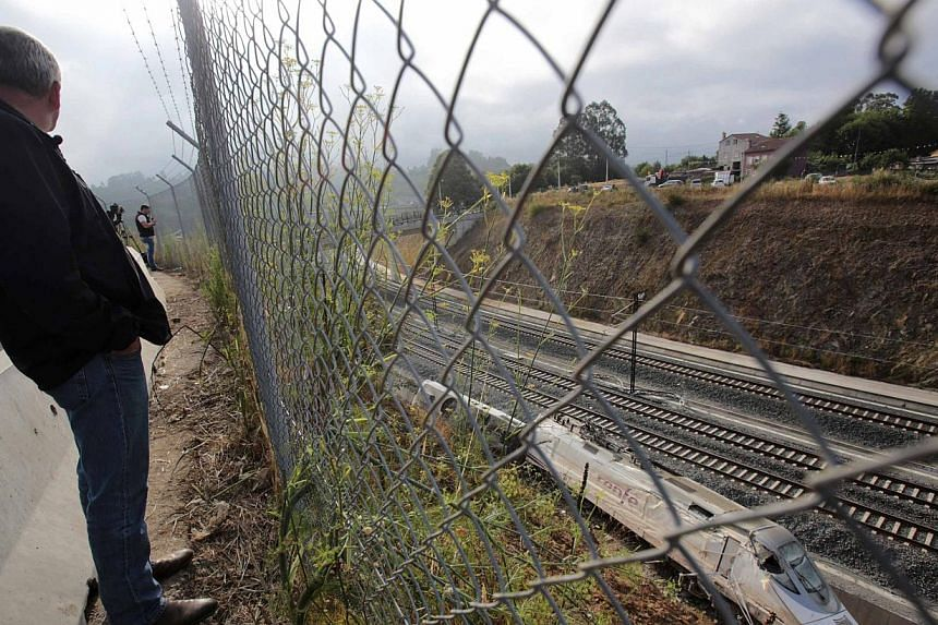A man looks the train engine at the site of a train crash in Santiago de Compostela, north-western Spain, on July 26, 2013. After the deadly high-speed train crash that struck on the rails below the nearby embankment on July 24, locals in Angrois, a