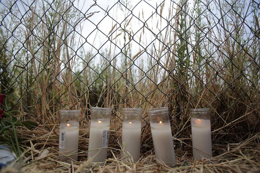 Candles are seen on July 26, 2013, at the site of a train crash in Santiago de Compostela, north-western Spain.After the deadly high-speed train crash that struck on the rails below the nearby embankment on July 24, locals in Angrois, a hamlet