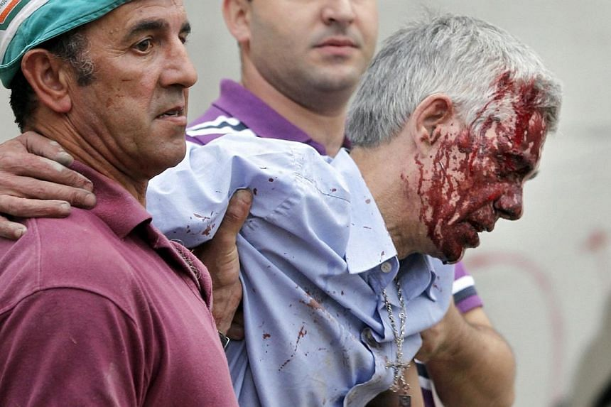 In this photo taken on Wednesday July 24 2013, train driver Francisco Jose Garzon Amo is helped by two men as he is evacuated from the site of a train accident in Santiago de Compostela, Spain. Mr Amo has refused to respond to police questioning on F